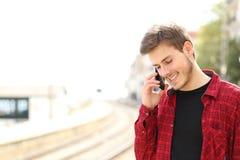 Jugendlich Kerl, der um den Handy wartet einen Zug ersucht Lizenzfreies Stockfoto