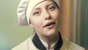 Jugendlich Kochmädchen, das ein Kuchen slowmo isst stock footage