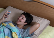 Jugendlich lachendes Mädchen bei der Prüfung ihrer Mitteilung auf tragbarem Gerät d stockfotografie