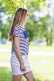 Jugendlich-Lebensstil-Konzepte und Ideen Blondes kaukasisches Jugendlich-Mädchen, das draußen im Park aufwirft Lizenzfreies Stockbild