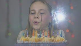 Jugendlich Mädchen brennt heraus Kerzen auf Kuchenkuchen auf ihrem Geburtstag durch stock video footage