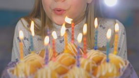 Jugendlich Mädchen brennt heraus Kerzen auf Kuchenkuchen auf ihrem Geburtstag durch stock video