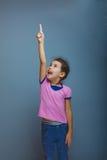 Jugendlich Mädchen, das auf den Himmel auf grauem Hintergrund zeigt Stockbilder