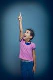Jugendlich Mädchen, das auf den Himmelgrauhintergrund zeigt Stockfotografie