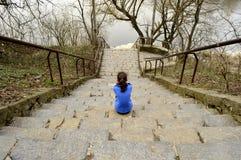 Jugendlich Mädchen, das auf den Schritten sitzt stockfoto