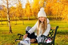 Jugendlich Mädchen, das auf Rollschuhe sich setzt Stockfotos