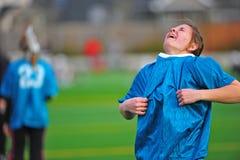 Jugendlich Mädchen, das auf Sport Jersey setzt Lizenzfreies Stockbild