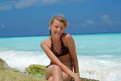 Jugendlich Mädchen, das auf Strand sitzt Stockfoto