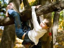 Jugendlich Mädchen, das am Baum hängt Lizenzfreie Stockfotos