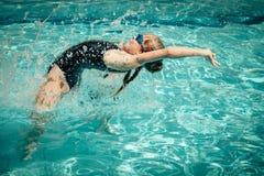 Jugendlich Mädchen, das in den Swimmingpool springt Lizenzfreie Stockfotografie