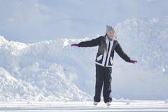 Jugendlich Mädchen, das gelockte Rochen und Winterkleidung an der Eisbahn trägt Lizenzfreie Stockfotos