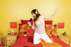 Jugendlich Mädchen, das im Schlafzimmer singt Lizenzfreies Stockbild