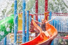 Jugendlich Mädchen, das im Swimmingpool auf Dia spielt Lizenzfreie Stockfotografie
