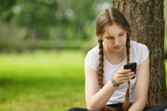 Jugendlich Mädchen, das nahe Baum mit Handy sitzt Lizenzfreie Stockfotografie