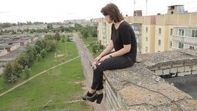 Jugendlich Mädchen, das am Rand des Dachs sitzt stock video