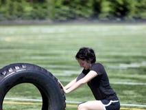 Jugendlich Mädchen, das schweren alten Reifen auf Sportfeld während des heißen Tages drückt stockfotografie