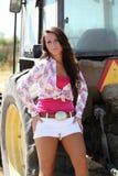 Jugendlich Mädchen, das am Traktor in den weißen Kurzschlüssen sich lehnt Stockfotos