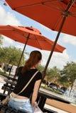 Jugendlich Mädchen, das unter Regenschirm sitzt Lizenzfreies Stockbild