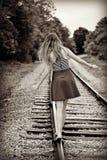 Jugendlich Mädchen, das weg auf ein Bahngleis geht Stockfotos