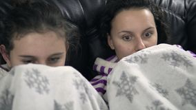jugendlich Mädchen in den pijamas, die auf der Couch mit Decke sitzen Stockfoto