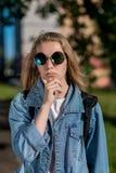 Jugendlich Mädchen in der Sonnenbrille, die an der Kamera aufwirft Kleidete jeden Tageskleidung Blonder Sommer in der Frischluft  Lizenzfreie Stockfotografie