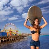 Jugendlich Mädchen des Brunettesurfers, das Surfbrett in einem Strand hält Stockbilder