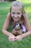 Jugendlich Mädchen des glücklichen Kindes, das mit Haustierwelpen lächelt Lizenzfreies Stockfoto