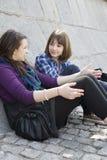 Jugendlich Mädchen, die auf Plasterung sitzen Lizenzfreies Stockfoto