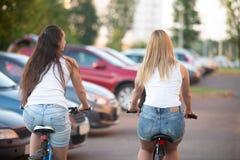 Jugendlich Mädchen, die in Stadt, hintere Ansicht radfahren Lizenzfreies Stockbild