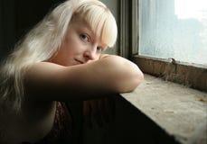 Jugendlich Mädchen durch Window Stockbild