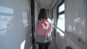 Jugendlich Mädchen geht auf ein Zugabteilauto mit einem Rucksack Reisetransport-Eisenbahnkonzept Kleines M?dchen-Gehen stock video footage