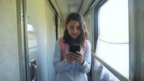 Jugendlich Mädchen geht auf ein Zugabteilauto mit einem Rucksack und einem Smartphone Reisetransport-Eisenbahnkonzept E stock video footage