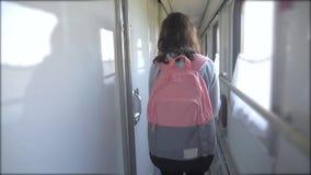 Jugendlich Mädchen geht auf ein Zugabteilauto mit Lebensstil einen Rucksack Reisetransport-Eisenbahnkonzept wenig stock video footage