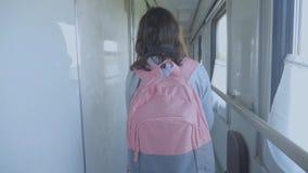 Jugendlich Mädchen geht auf ein Zugabteilauto mit Lebensstil einen Rucksack Reisetransport-Eisenbahnkonzept wenig stock video