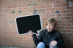 Jugendlich Mädchen hält schwarzes Zeichen Lizenzfreies Stockfoto