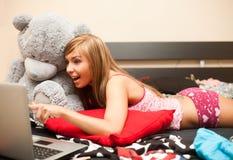 Jugendlich Mädchen im Bett mit Laptop Lizenzfreies Stockbild