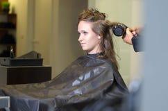 Jugendlich Mädchen im Salon, der ihr Haar mit Schlag-Trockner trocknet Stockbilder