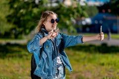 Jugendlich Mädchen im Sommer in einem Park draußen In der Sonnenbrille in den Händen macht das Halten des Telefons ein Person ` s Lizenzfreie Stockfotografie