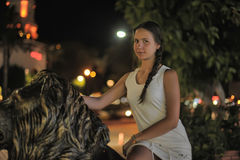 Jugendlich Mädchen im weißen Kleid nahe bei der Skulptur eines Löwes Lizenzfreies Stockfoto