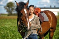Jugendlich Mädchen mit dem braunen Pferd Lizenzfreie Stockfotos