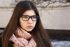 Jugendlich Mädchen mit dem langen braunen Haar in den Eyewearmyopiegläsern Stockfotos