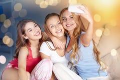 Jugendlich Mädchen mit dem Smartphone, der zu Hause selfie nimmt stockfotos