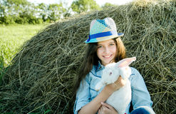 Jugendlich Mädchen mit dem weißen Kaninchen, das vor Heuschober sitzt Stockfoto