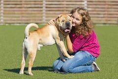 Jugendlich Mädchen mit einem Hund auf dem Fußballplatz Lizenzfreies Stockfoto