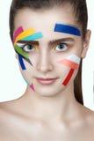 Jugendlich Mädchen mit farbigen Streifen auf dem Gesicht Helle Make-upkunst Stockbild