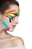 Jugendlich Mädchen mit farbigen Streifen auf dem Gesicht Helle Make-upkunst Stockfotografie