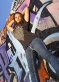 Jugendlich Mädchen mit Graffitiwandhintergrund Stockbild