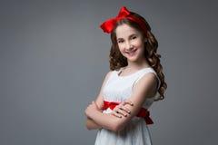 Jugendlich Mädchen mit rotem Bogen auf Kopf Lizenzfreie Stockbilder