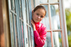 Jugendlich-Mädchen schaut heraus das landwirtschaftliche Haus des Fensters Lizenzfreies Stockbild