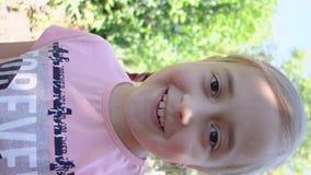 Jugendlich Mädchen steht auf Videoschwätzchen in Verbindung und bewegt seine Hand wellenartig und sagt Guten Tag Vertikales Schie stock video footage